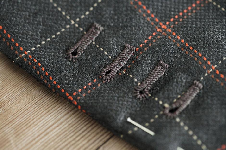 Detailaufnahme von handumsäumten Knopflöchern eines maßgeschneiderten Seidenanzugs