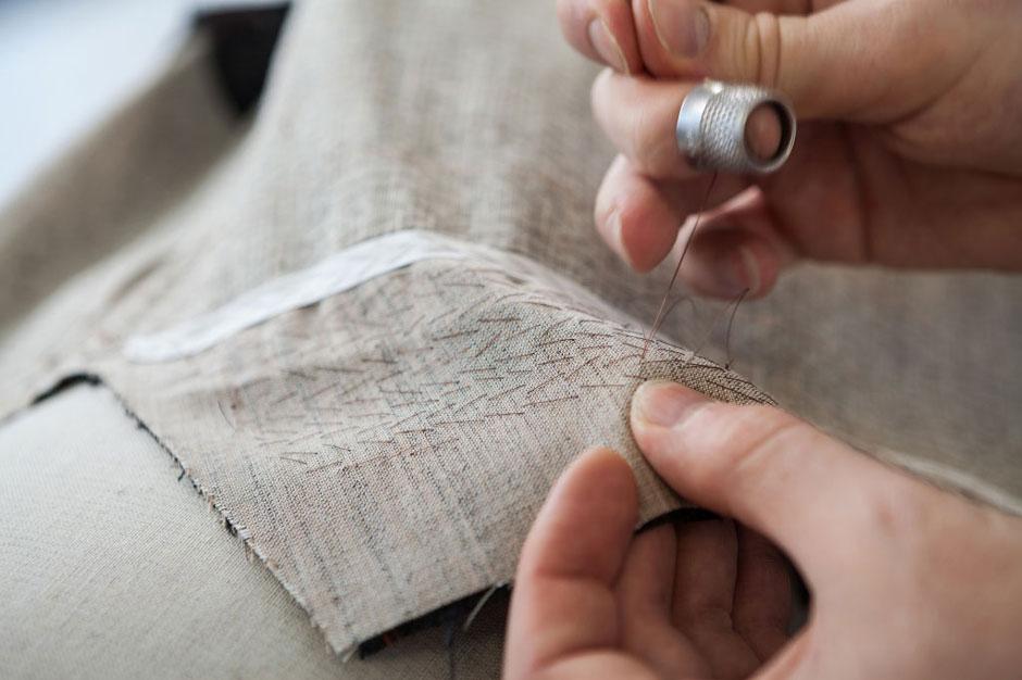 Das Pikieren von Hand ermöglicht das elegante Ausrollen des Revers auf dem Schließknopf