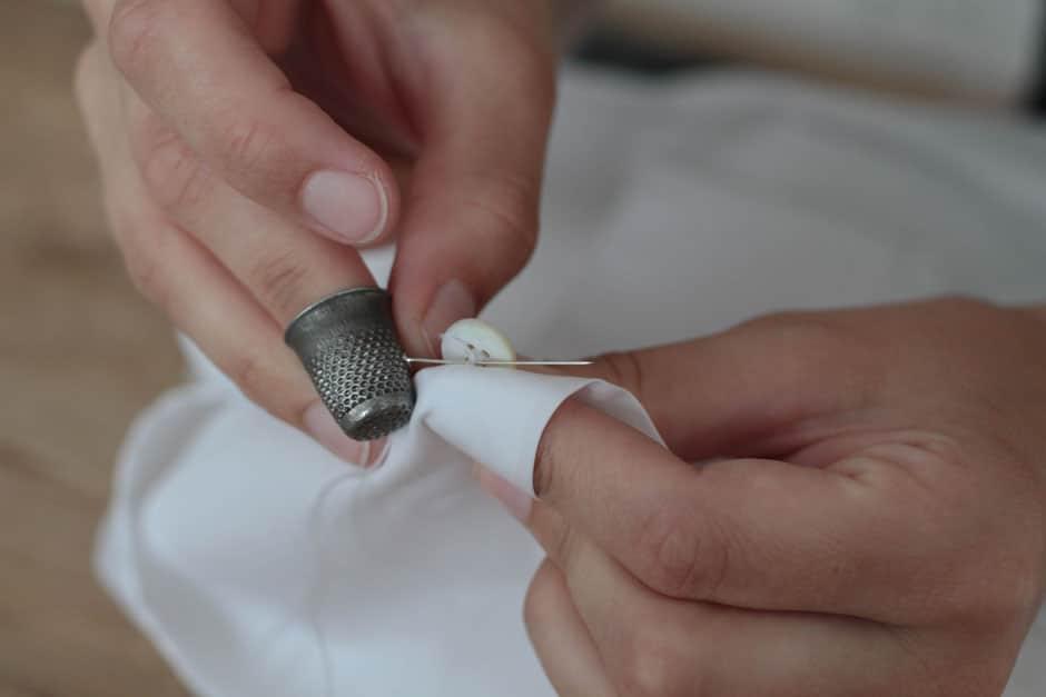 Von Hand angenähter Perlmuttknopf eines Maßhemds